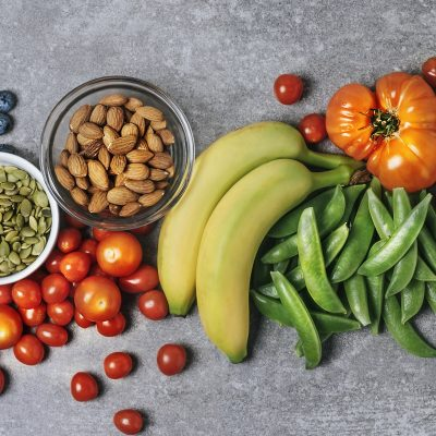Fresh vegetables, fruits, and nuts on gray background