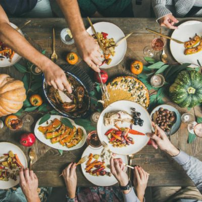 Traditional Thanksgiving or Friendsgiving holiday celebration party. Flat-lay of friends or family feasting at Thanksgiving Day festive table with turkey, pumpkin pie, roasted seasonal vegetables and fruit, top view.